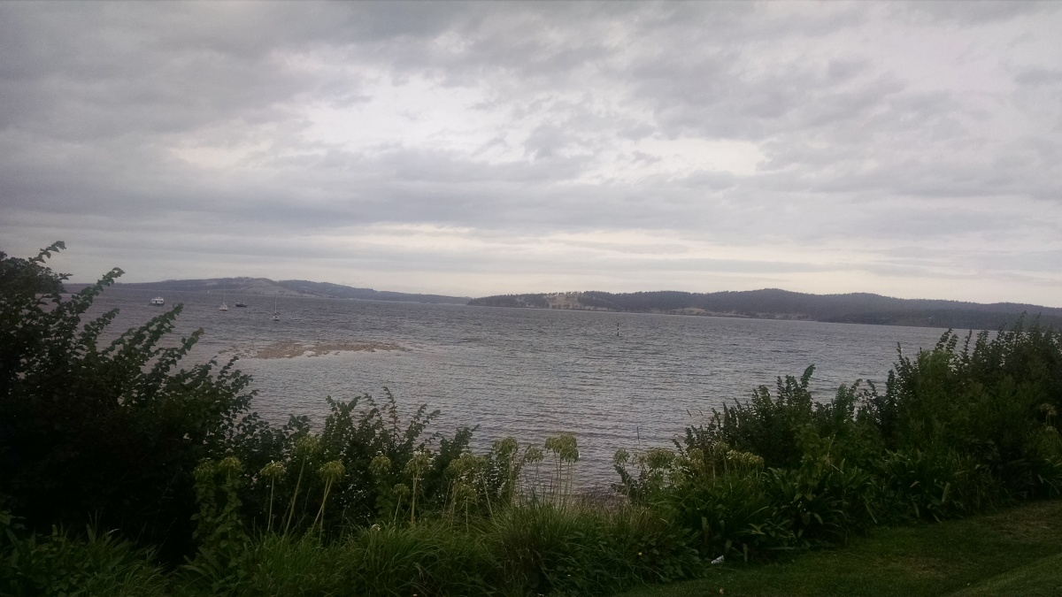 View of a grey Derwent River, with cloudy skies. Bruny Island is in the distance.