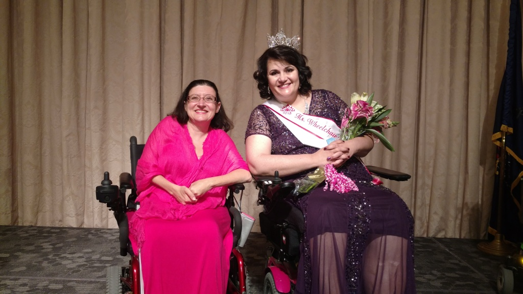 Two women seated in wheelchairs. One is wearing a pink dress and shawl. The other is wearing a purple dress, a sash and crown and holds a bouquet of flowers. Both are smiling.