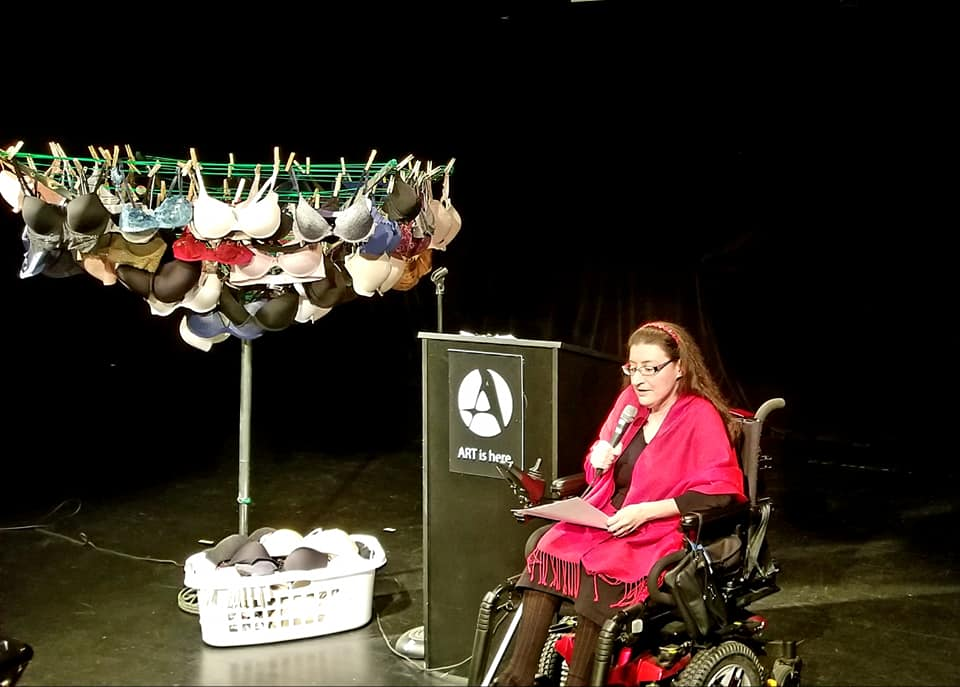A woman wearing a red cape is seated in a wheelchair in front of a podium. She is reading into a microphone. There is an indoor circular clothesline with various color bras hanging on it on the other side of the podium.